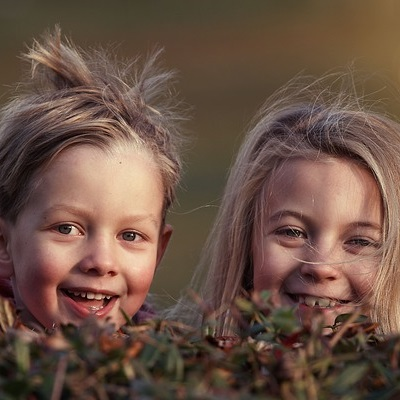 Two children smiling in the autumn leaves