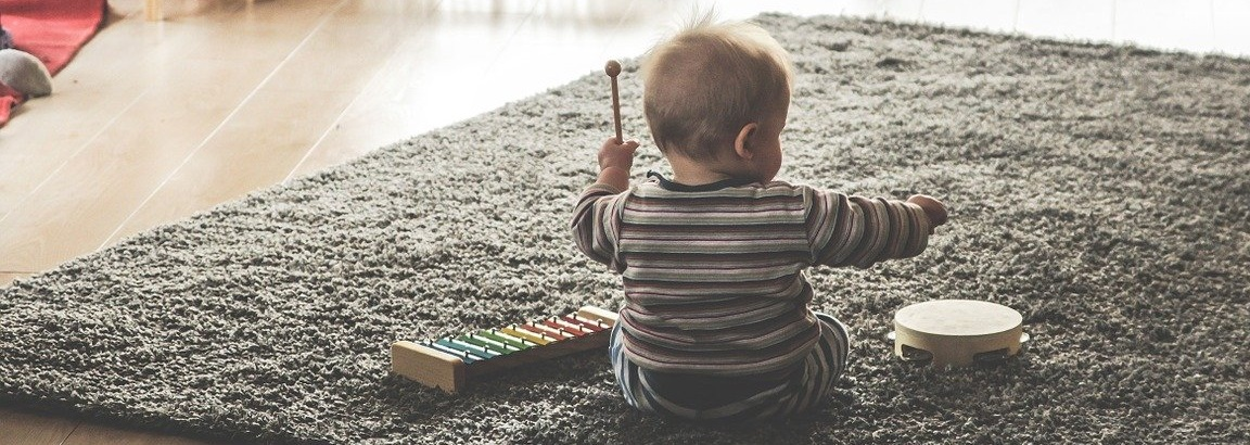 The back of a small child playing musical instruments